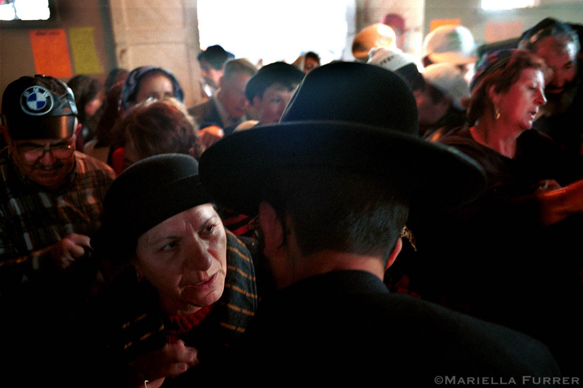 A Jewish pilgrims  leans over the tomb of Rabbi Abu Hatzeira to talk to a man.