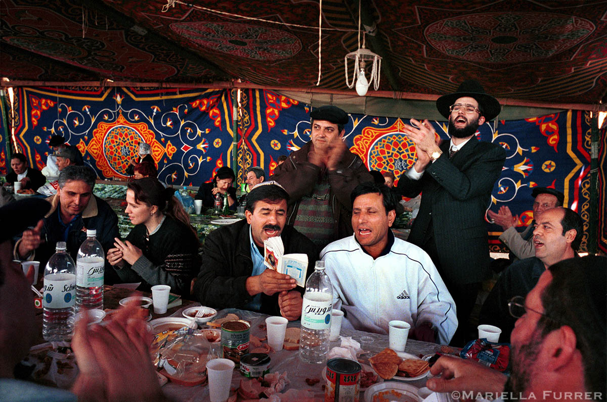 A group of Jewish pilgrims clap and sing at their table outside the shrine of Rabbi Abu Hatzeira.
