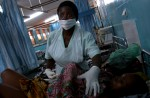Hlalapi Kunkeyani, a registered nurse in charge of the maternity ward at Bottom Hospital in Lilongwe tends to a mother and her new born baby. May 2004