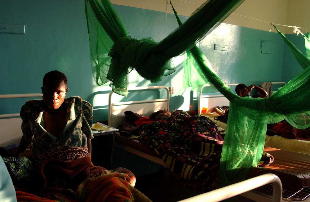 Exhausted after child birth, women lie in bed beneath mosquito nets in the post-natal ward at Bottom Hospital in Lilongwe. May 2004