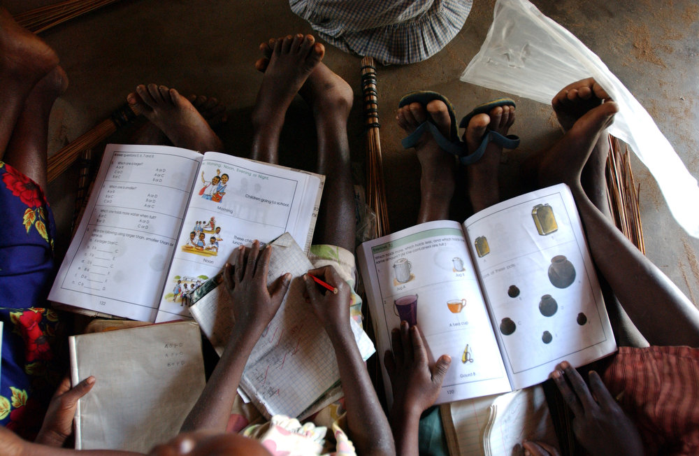 Due to the lack of school desks and chairs, standard one students use their legs to work on during an afternoon class at the Gahaleni Primary School