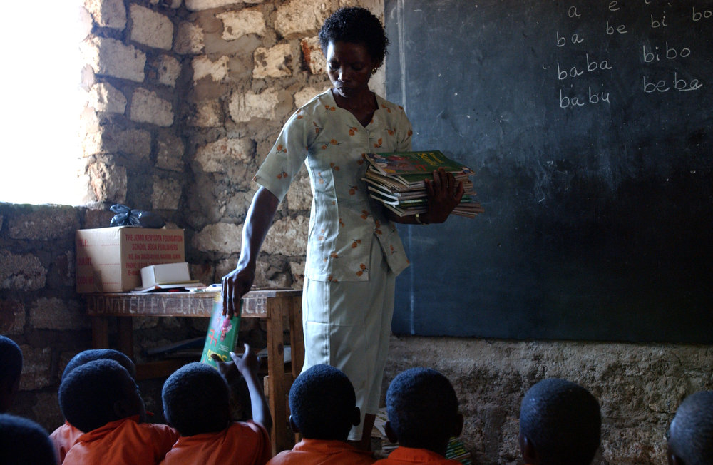Rebecca Mwanyonyo, 35yrs and teacher of standard one students at the Gahaleni Primary School, distributes text books to her pupils. Children share a book between three of them.