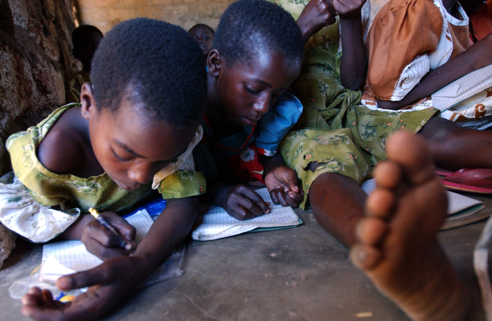 Due to the lack of desks and chairs in the class, standard one students write on the floor during an afternoon class at the Gahaleni Primary School.