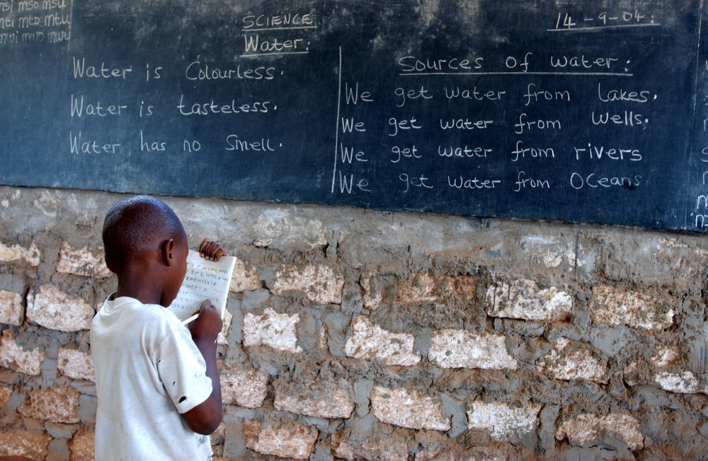 A standard one student stays behind after class is dismissed to copy off the board at the Kadzuhoni Primary School.