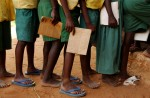 Standard students queue up to get their books marked at the Kadzuhoni Primary School. Many students can't afford school uniform and most go to school barefoot.