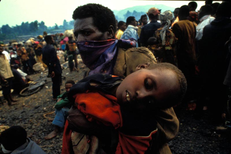A man carries his son to the MSF camp during a Cholera epidemic which killed an estimated 50'000 Rwandan Refugees in Zaire, now the Democratic Republic of Congo. July 1994