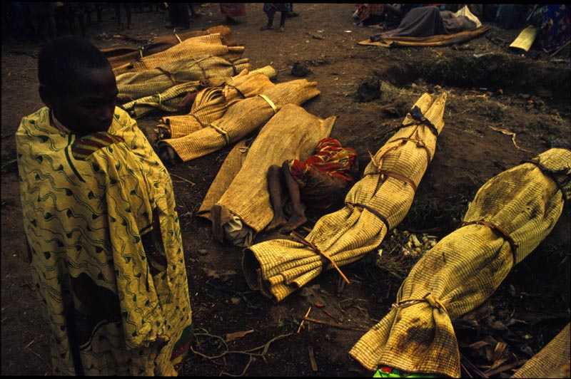 A young boy walks passed bodies, rolled up in mats, waiting to be picked up and buried in mass graves during a Cholera epidemic which killed an estimated 50'000 Rwandan Refugees in Zaire, now the Democratic Republic of Congo. July 1994