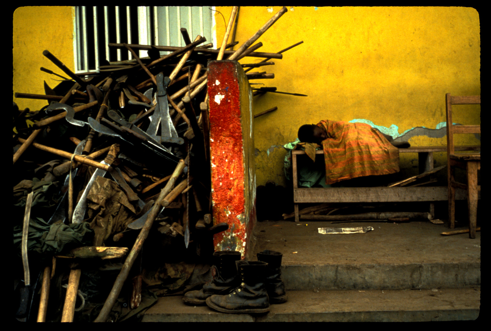 A young boy sleeps on a bench beside piles of machetes confiscated by the Zairean military as Rwandan refugees, mainly Hutus, fled across the border into Zaire, now the Democratic Republic of Congo. July 1994