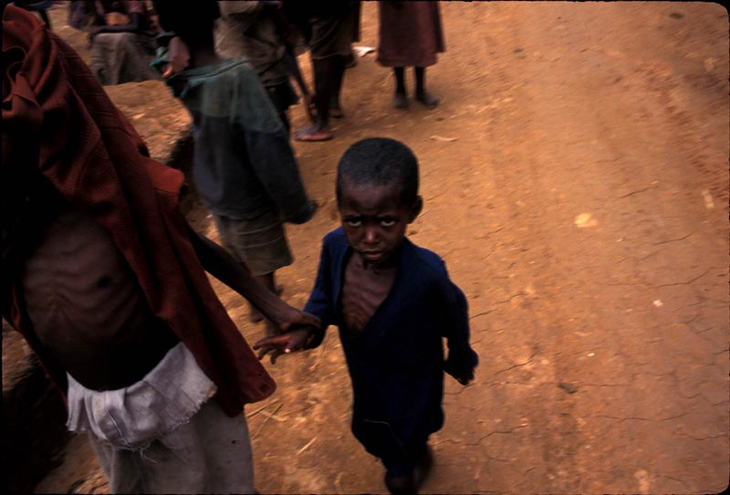 A young Hutu boy and his mother return to Biaro refugee camp in the Democratic Republic of Congo weeks after fleeing when the camp came under attack by Rwandan and DRC military. The refugees that weren't killed returned emactiated and with terrible injuries. May 1997