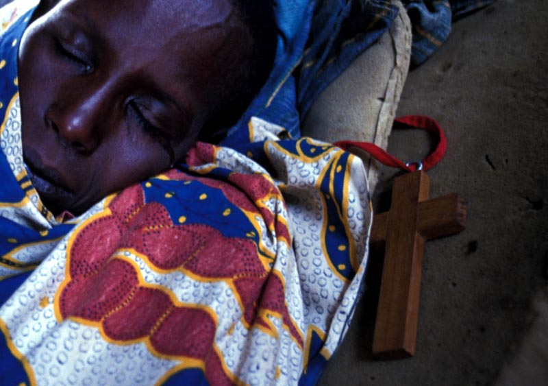 A Tutsi woman in hiding sleeps with a cross by her side. She and her family fled and were hiding in a warehouse. Rwanda, May 1994.