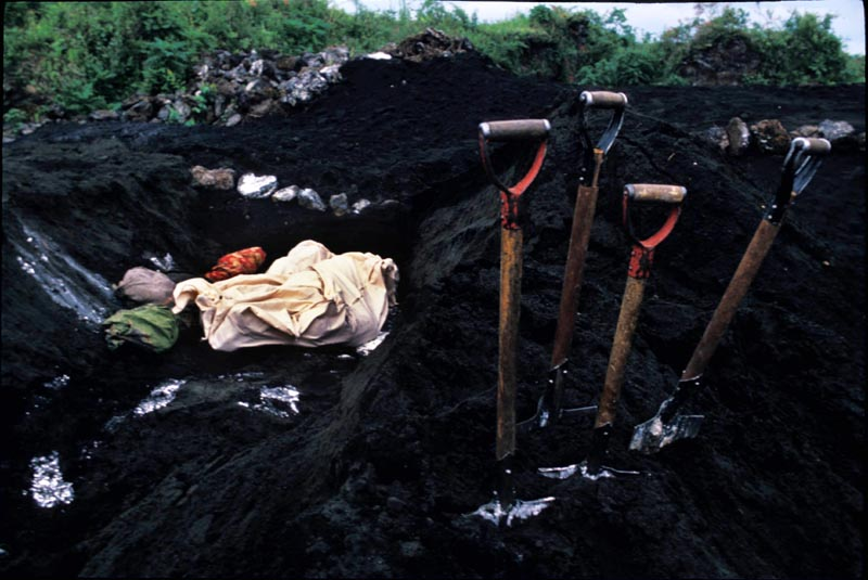 Mass grave is dug in larva rock for Rwandan refugees died of cholera. Goma, Zaire, July 1994.