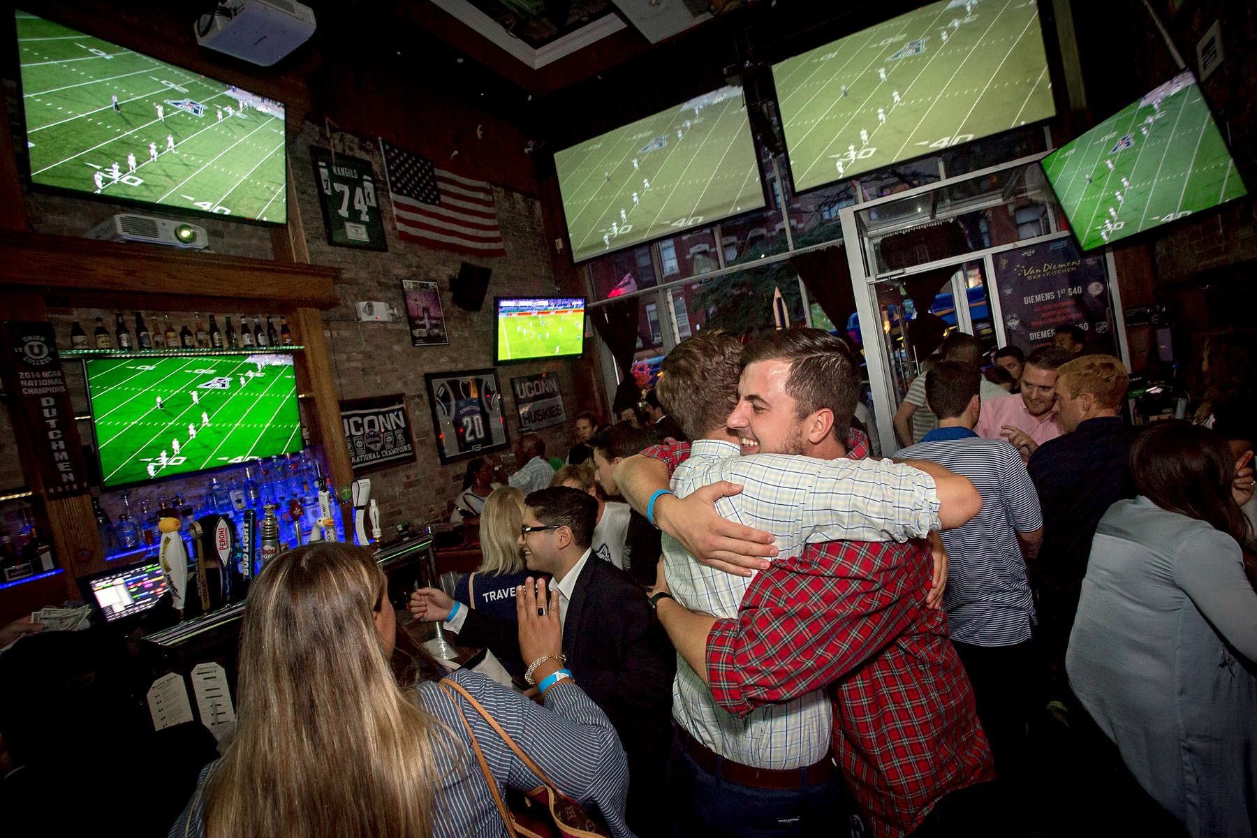 Alumni embrace during a Welcome to the Neighborhood UConn football watch party at Van Diemens bar Thursday, August 31, 2017 in New York City. (G.J. McCarthy / UConn Foundation)