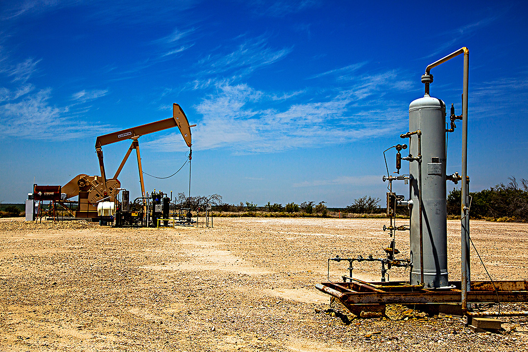 An oil pumpjack works in the background by natural gas machinery in this photo taken Tuesday, May 6, 2014 in Webb County, Texas.