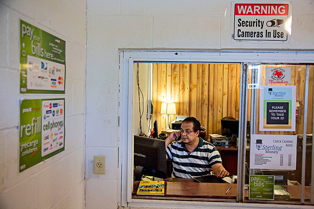 T.J. Ramos, owner of Sterling Money Services, takes a phone call at his business Tuesday, May 6, 2014 in Carrizo Springs, Texas. Ramos, a Laredo native, commutes nearly an hour each way to run his check cashing service, which maintains a steady flow of business from natural gas workers in the region.