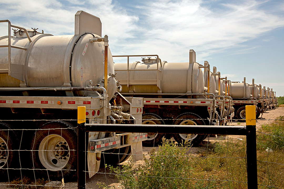 A row of natural gas trucks parked on the site of a well Tuesday, May 6, 2014 in Webb County, Texas.