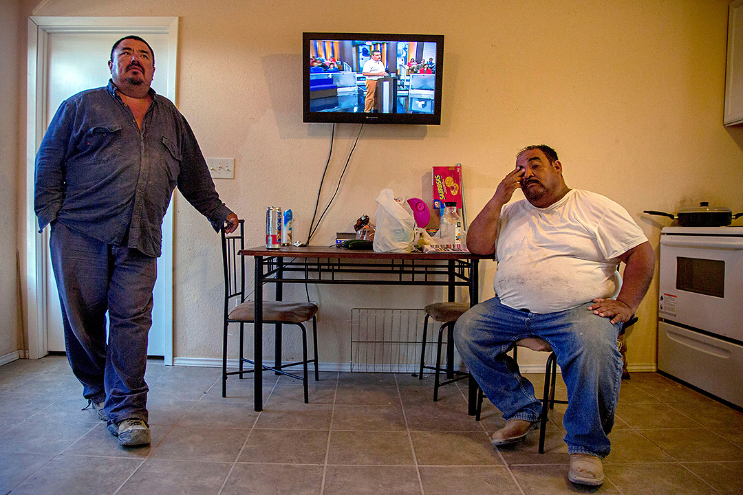 Juan Jimenez (left) and Manuel Uresti relax in their trailer after a long day of working gas wells Tuesday, May 6, 2014 in Dimmit County, Texas. The men, who are natives of Mission, Texas, are living in a {quote}man camp{quote} in Carrizo Springs. The camps, which are found all across the south Texas region, house transient oil and gas workers who have come to the area to work the Eagle Ford Shale.