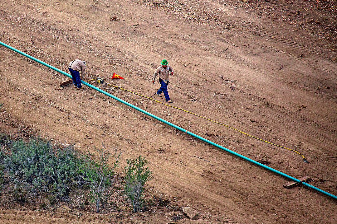 Workers lay a natural gas pipe across the ground near a natural gas drilling site Wednesday, May 7, 2014 in Webb County.