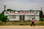 A woman walks by an abandoned storefront Wednesday, May 7, 2014 in Big Wells, Texas.