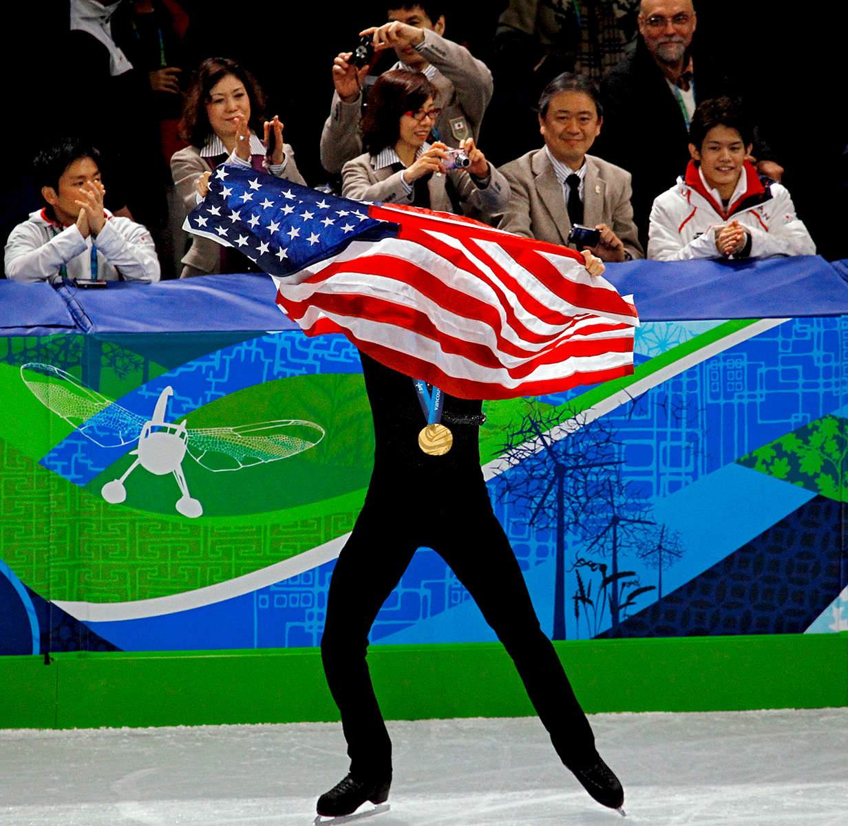 The United States' Evan Lysacek is applauded as he takes a victory lap with the American flag and his gold medal in the men's figure skating final during the 2010 Winter Olympic Games at Pacific Coliseum in Vancouver, British Columbia, Canada.