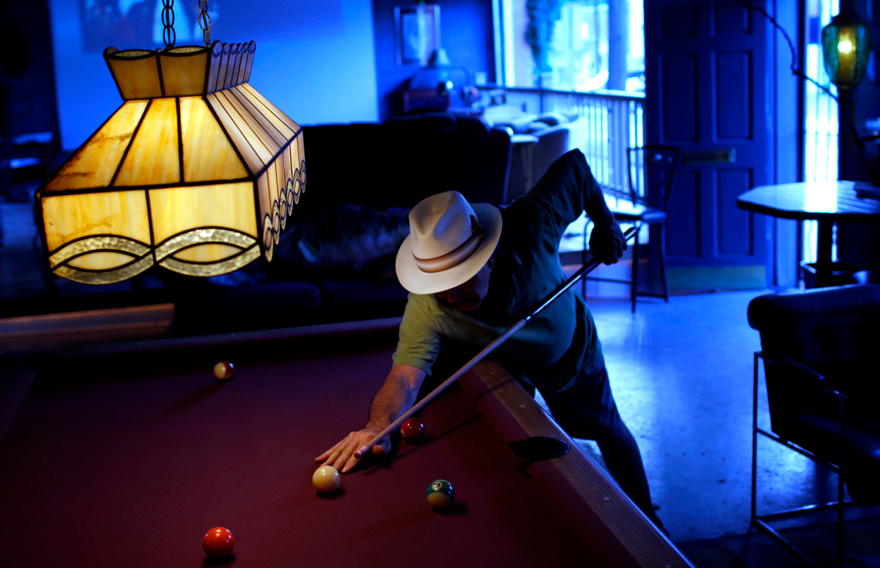 Ron Patterson lines up a shot as he plays pool in his {quote}man cave{quote} in Dallas. In 1999 Patterson and his wife purchased a home on West Seventh Street that included a former auto garage with a storefront on parallel West Davis Street. Over the past several years Patterson has transformed the garage, which was once one of many along West Davis Street, into a large den that includes a full bar, fireplace, and large screen projection television.