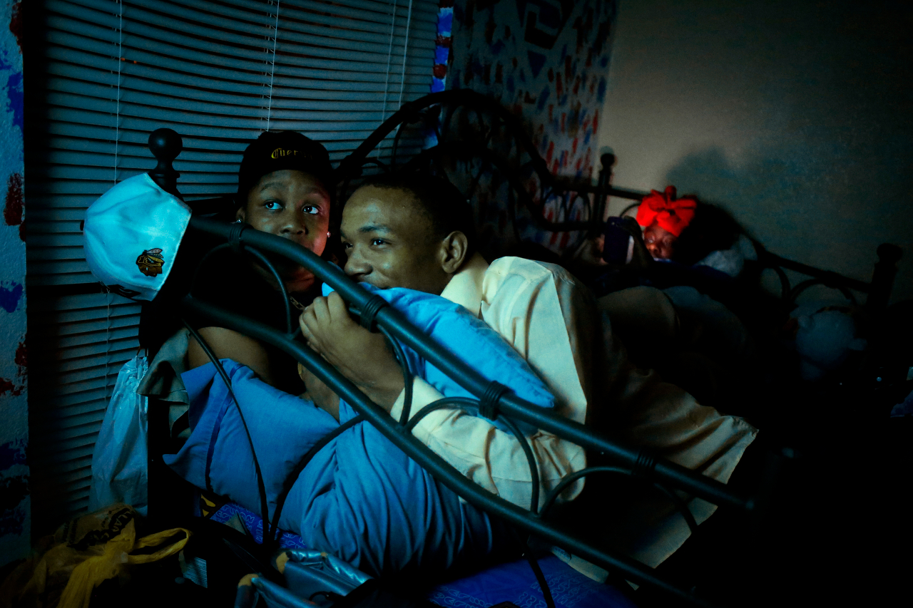 Victoria Savage (left) and J.T. Armstead (center) watch a scary movie as Armstead's cousin, Jenett'e Brooks, plays on her mobile phone at their home in Duncanville, Texas.