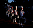 Members of the Bullard High School marching band walk through a shaft of late evening light at Fair Park as they head to a performance during the State Fair of Texas in Dallas.