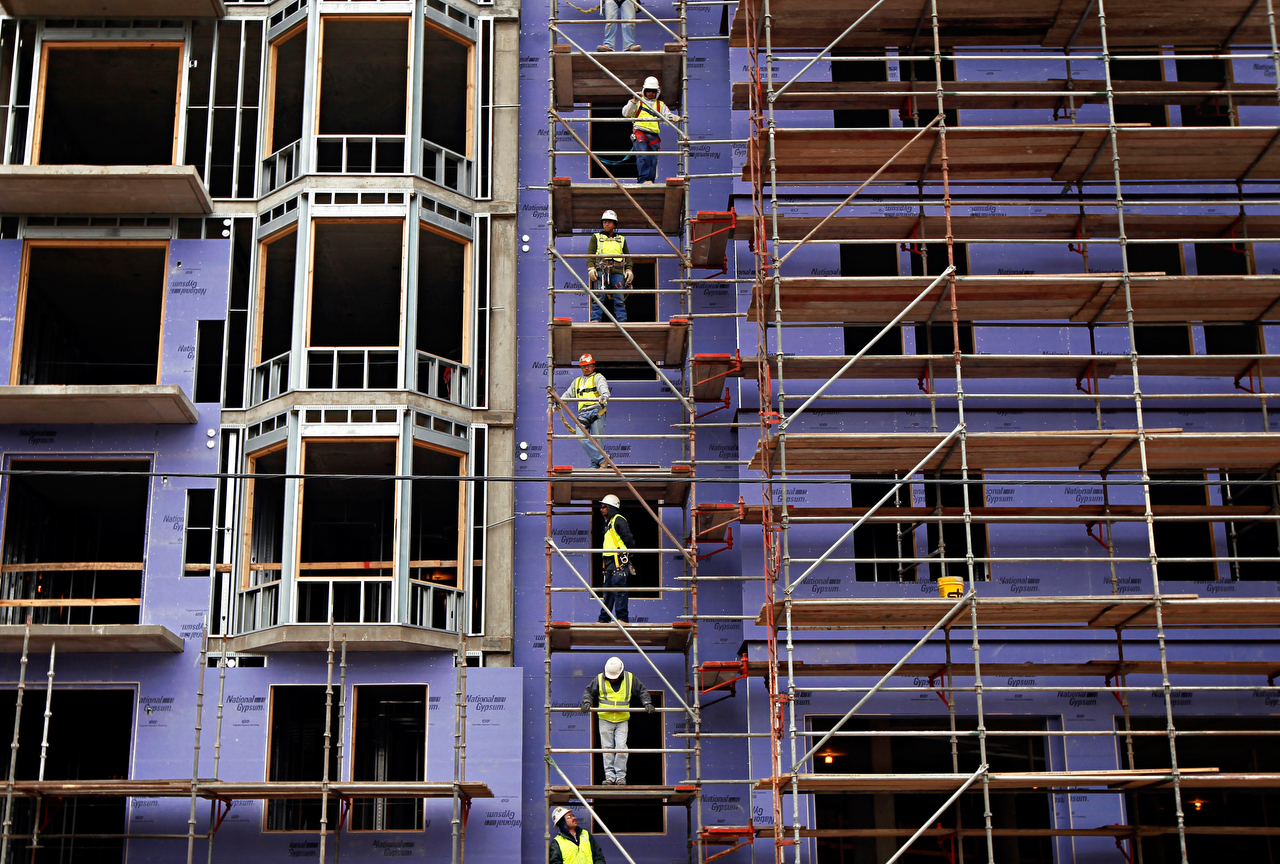 Workers stand on scaffolding at the Gables Katy Trail apartment complex, which is currently under construction in the Uptown neighborhood of Dallas.