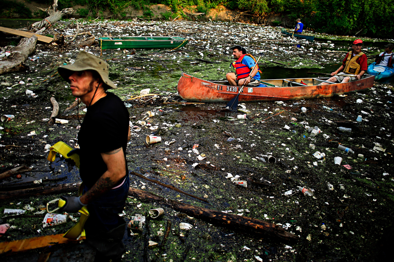 Jon McCurley (far left) looks on as he and other volunteers skim the littered waters of White Rock Creek in northeast Dallas, Texas. Dozens of participants spent the morning collecting trash around the creek area by foot and kayak.