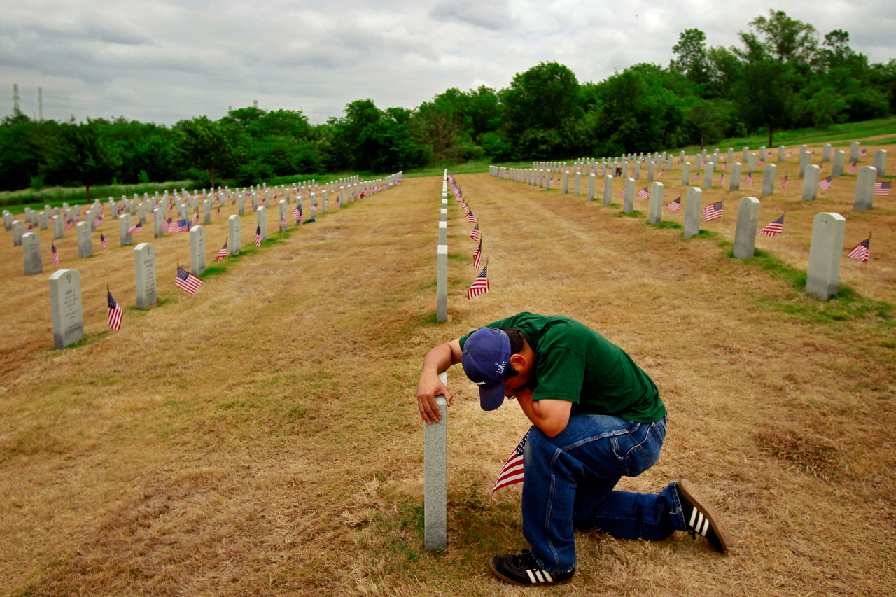 Ernest Chavarria is overcome with emotion as he visits the grave of his father, Daniel Gonzalez, during the annual Memorial Day Ceremony at the Dallas-Fort Worth National Cemetery in southwest Dallas, Texas. Chavarria, a resident of Oak Cliff, regularly visits his father's final resting place, where he often plays him music they enjoyed together through headphones of his portable music player, which he places against the tombstone. {quote}He taught me values,{quote} says Chavarria of his father, who served in the United States Marine Corps during the Vietnam War. {quote}He was the smartest man I ever new. He made me the man that I am today.{quote}