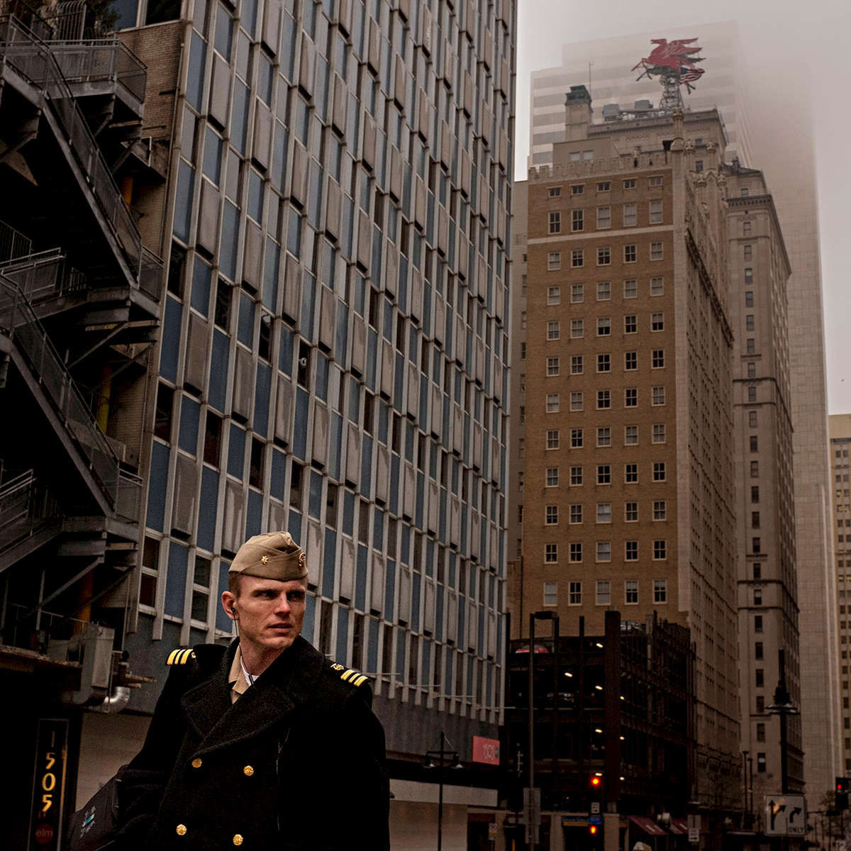 Mist settles over downtown as Lt. Cmdr. Shad Schopper of the U.S. Public Health Service walks up Elm Street to a DART stop in Dallas.