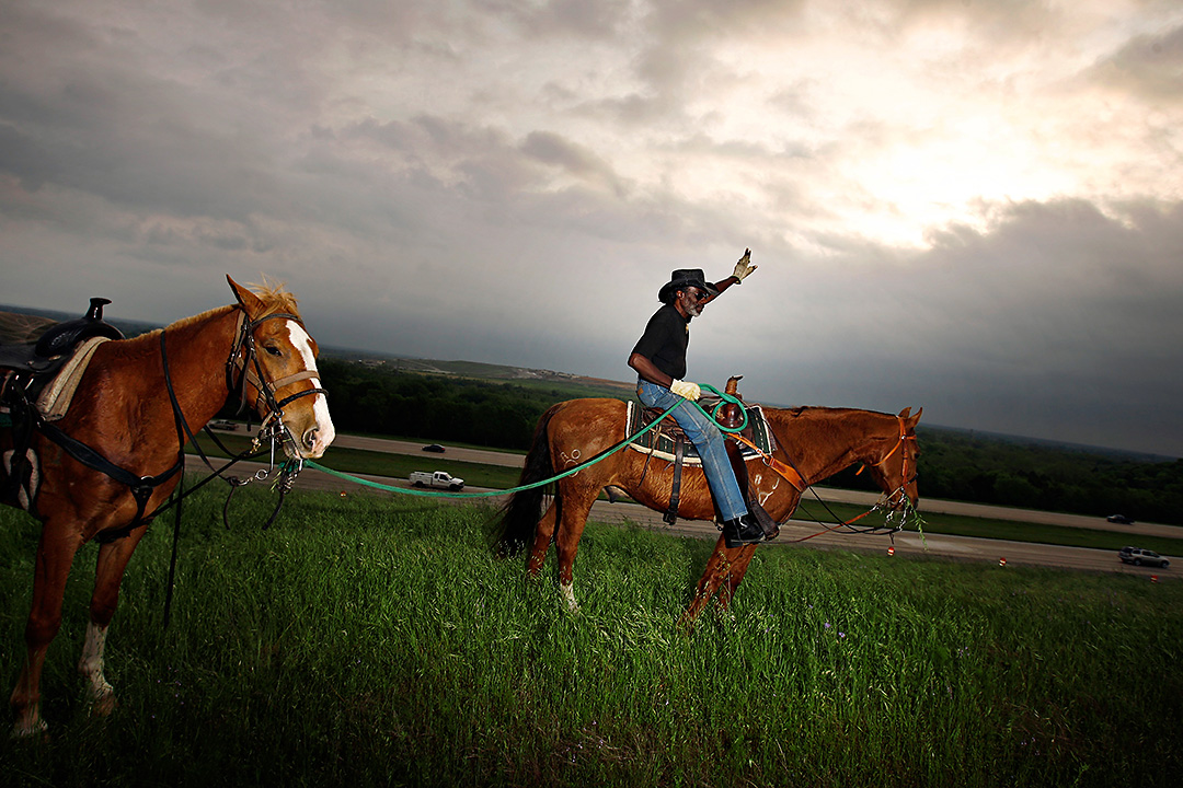 Riding atop his 18-year-old horse, Roc, B.J. Brantley waves at traffic on I-45 as he walks 7-year-old Tennessee April 24, 2009 in south Dallas. For the last seven years, Brantley had ridden horses along the I-45/I-20 interchange during morning rush hour. Known as the {quote}Interstate Cowboy,{quote} the 66-year-old said he performs the daily activity to inspire at-risk youth in the area. {quote}It done turned into a full-blown mission,{quote} he said. {quote}When I see that kid's face light up, that makes my day.{quote}