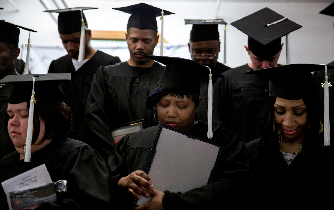Janice Hensley (center) and classmates bow their heads in prayer during a graduation from the LIFE Program Monday, February 16, 2015 at the Dallas Life Foundation in Dallas. Hensley and her husband, Kenneth Davis, graduated from the 10-month-long program while living at the shelter for more than a year. They were joined at Dallas Life by three of their children.