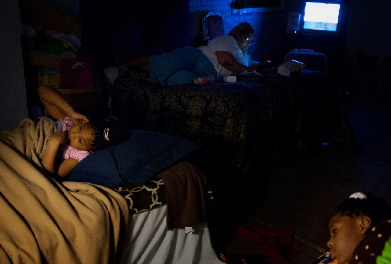 Lyric Davis (left) and her sister, Ken'Tajiah (right) lay in their beds awaiting sleep with their mother, Janice Hensley, watches TV in the background in their small room at the Dallas Life Foundation Wednesday, March 18, 2015 in Dallas. The family of five have been living at the homeless shelter since April 2014.