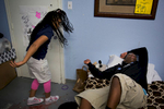 Lyric Davis (left) throws items on the floor in an attempt to wake her brother, Milton Hensley, in their room at the Dallas Life Foundation Wednesday, March 18, 2015 in Dallas. The family of five has been living in a small room at the shelter since April 2014.