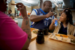 Kenneth Davis (center) jokes with his daughter, Lyric, while they eat dinner at the Dallas Life Foundation shelter Thursday, March 19, 2015 in Dallas.