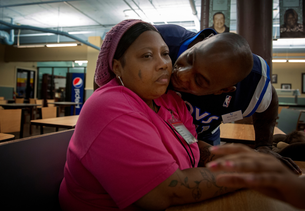Janice Hensley (left) is lost in thought as her husband, Kenneth Davis, kisses her cheek in the cafeteria at Dallas Dallas Life Foundation Wednesday, March 18, 2015 in Dallas. The couple and three of their children have been living at the homeless shelter since April 2014. Janice says the experience has tested their marriage.