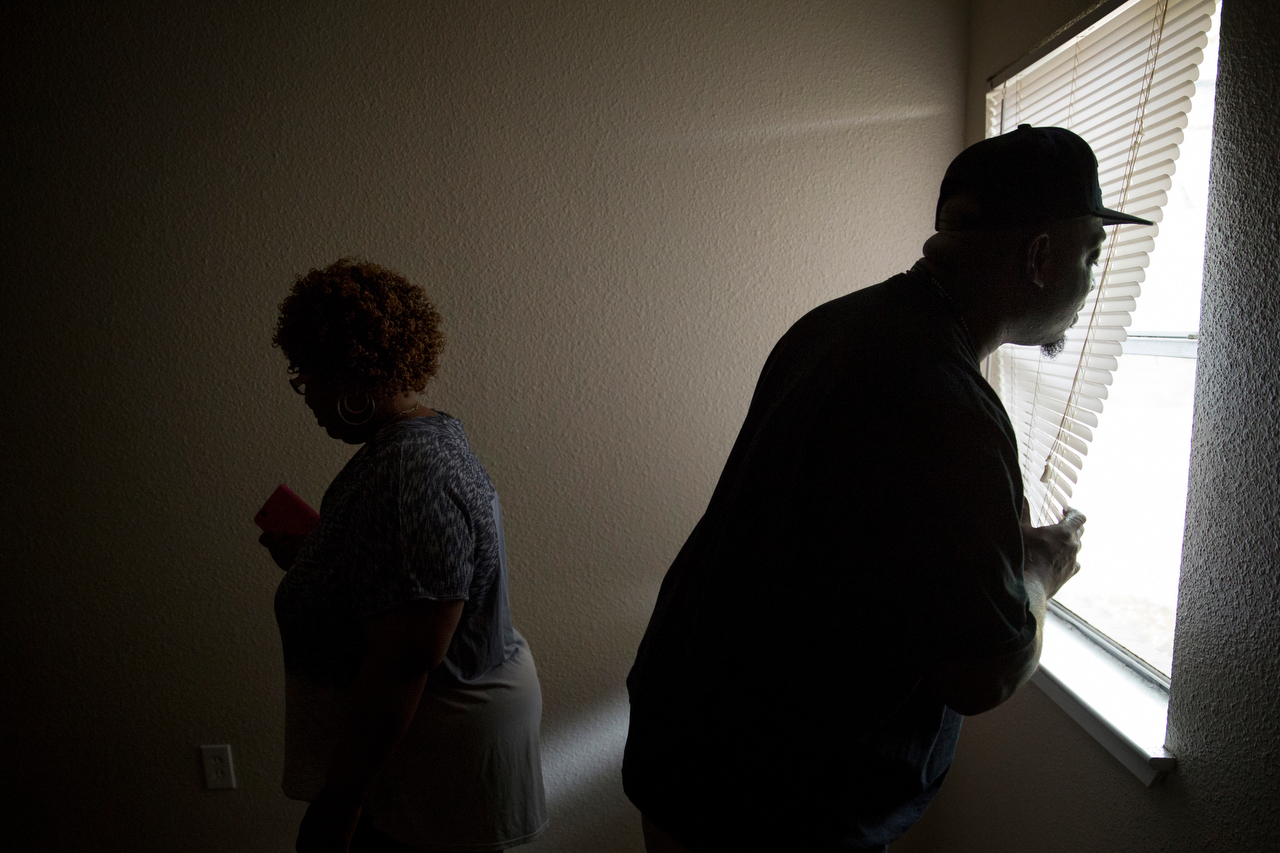 Kenneth Davis (right) looks out of blinds in the master bedroom as he and his wife, Janice Hensley, check out their new apartment Friday, April 17, 2015 in northeast Dallas. The couple and three of their children have been living at the Dallas Life Foundation homeless shelter for more than a year. Through the help of Family Gateway, the were able to secure their first apartment since becoming homeless.