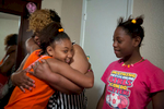 Ken'Tajiah Davis (right) watches as her sister, Lyric, hugs their mother Janice Hensley on the first day at their new apartment Wednesday, April 29, 2015 in northeast Dallas. After more than a year of living at the Dallas Life Foundation homeless shelter, the family moved in to their new apartment.