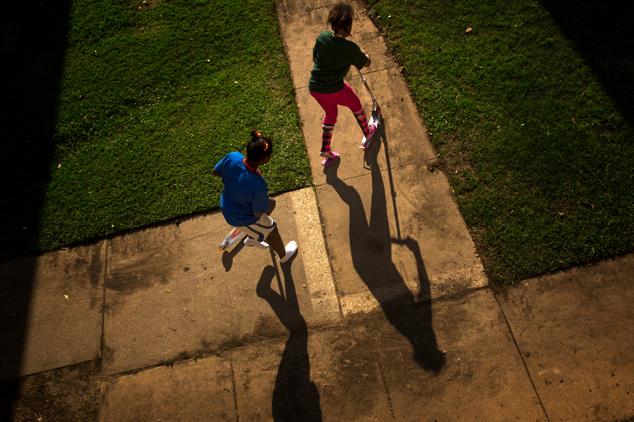 Ken'Tajiah Davis (left) and her sister, Lyric, play on scooters outside their new apartment Wednesday, April 29, 2015 in northeast Dallas. After more than a year of living at the Dallas Life Foundation homeless shelter, the family moved in to their new apartment.