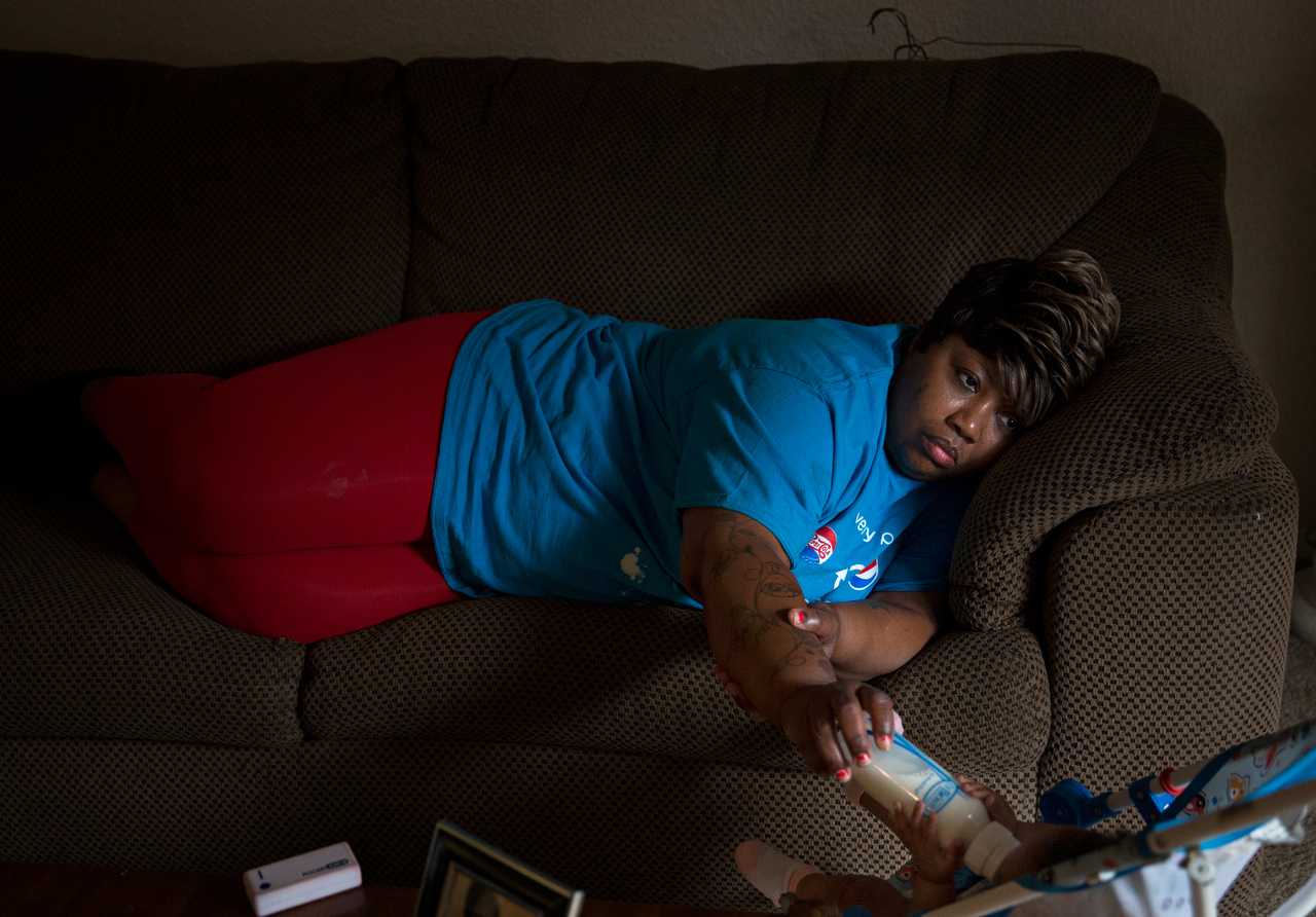 After a long day of work, an exhausted Janice Hensley lays on the couch while feeding her granddaughter, Faith, in her apartment Tuesday, May 12, 2015 in northeast Dallas. Hensley and her family have been living in their new apartment for a few weeks after spending more than a year at a homeless shelter.
