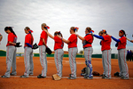 Members of the North Central Texas College softball team take part in a moment of silence before their season opener against Southwestern Assemblies of God in Gainesville, Texas. Four players on the team were killed last September after a bus they were riding in was hit by an 18-wheel truck in Davis, Okla.