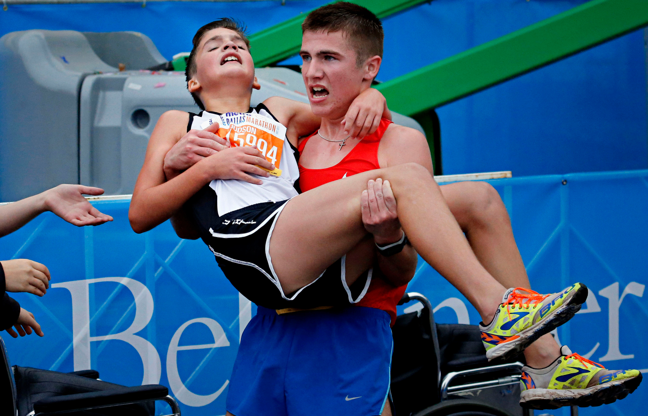 Trace Greer (right) carries his exhausted brother Judson Greer after the Melissa, Texas siblings crossed the finish line together in the half marathon during the MetroPCS Dallas Marathon in Dallas, Texas.