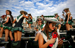 Tori Tew uses a hand fan to cool off as she and other members of the Emerald Belle dance troop wait for the start of Southlake's game against Austin Westlake at Dragon Stadium in Southlake, Texas.