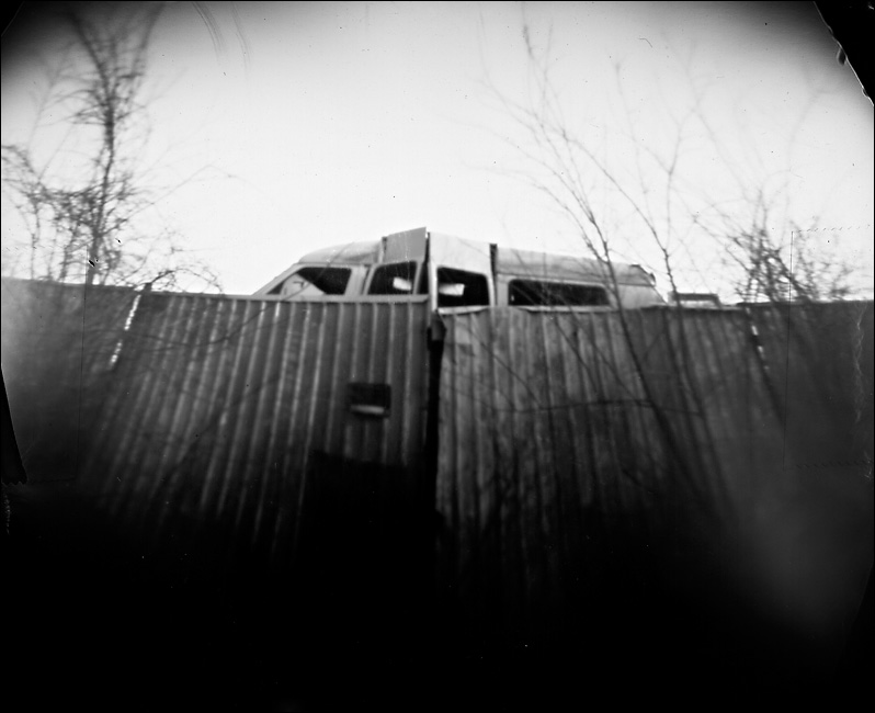 Junk yard van and old fence off far South Lamar in Dallas, taken on March 7, 2009 with soda bottle camera. Three minute, 30 second exposure on RC photo paper.