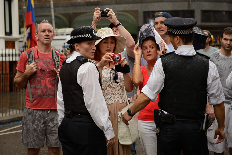 Tourists encounter Julian Assange demonstration.