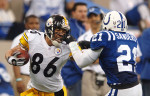Indianapolis, Indiana.    Pittsburgh Steelers wide receiver Hines Ward finishes off a 40-yard completion while getting his face mask grabbed by Safety Bob Sanders  during an AFC Dvisional playoff game at the RCA Dome on January 15th, 2006. / Vincent Pugliese