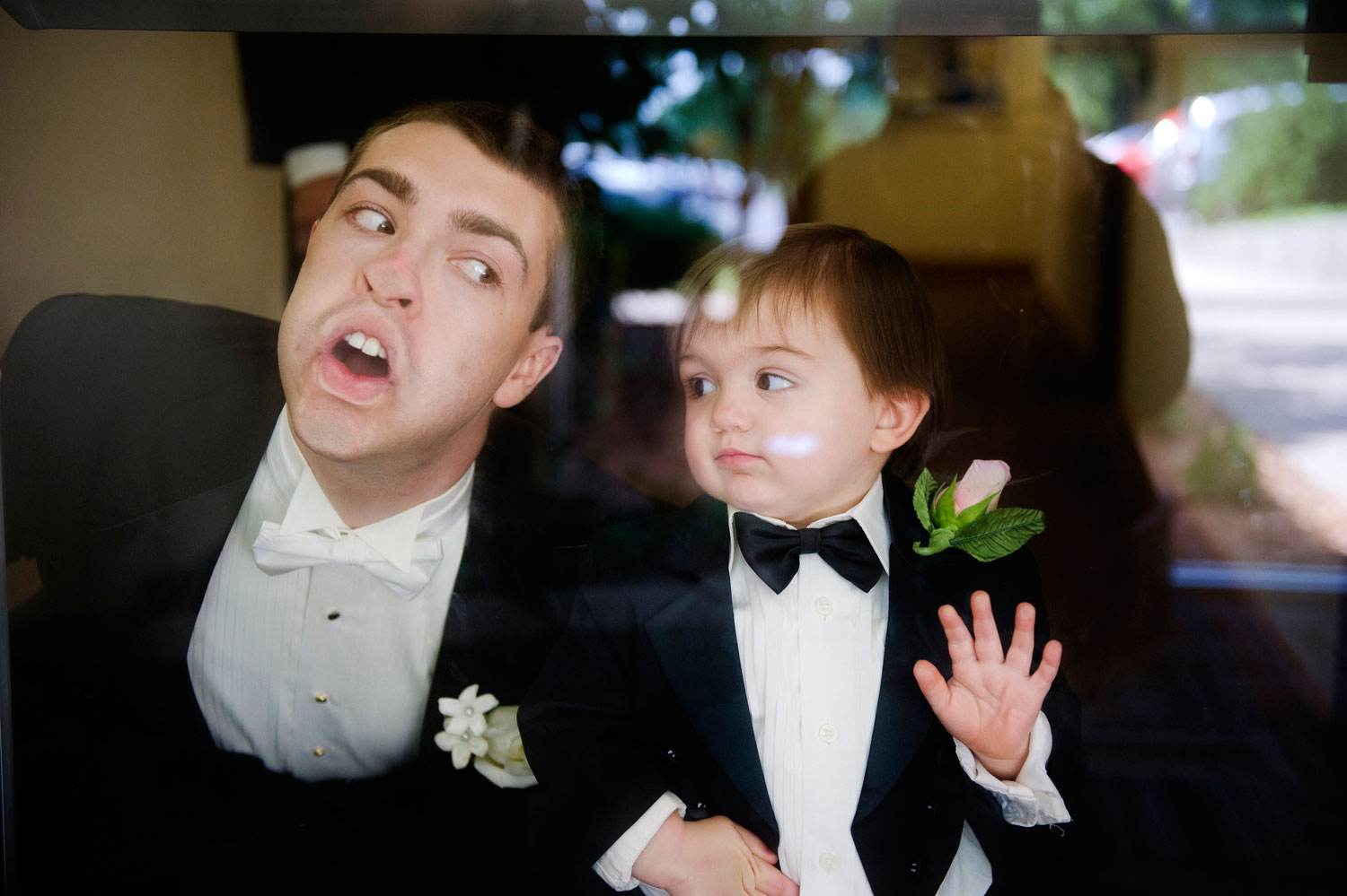 A groom and his ring bearer joke around while making silly faces into the glass while being photographed by pittsburgh wedding photographers Elizabeth Vincent Photography prior to their wedding reception at The Grand Concourse in downtown Pittsburgh, Pennsylvania.