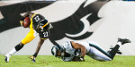 Philadelphia, PA.   Under the watchful eagle eye in the background, Pittsburgh Steelers rookie running back Chris Rainey breaks a tackle during the Steelers first preseason game of 2012 against the Philadelphia Eagles at Lincoln Financial Field in Philadelphia, Pennsylvania./ Vincent Pugliese