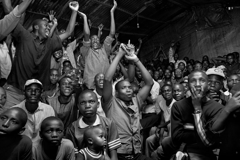 Love of football is instilled in Mathare Valley children at a young age. When Kenyans' two most beloved English clubs, Manchester United and Arsenal, locked horns in the 2005 FA Cup Final, Mathare Valleyyouths packed Wembley Video Hall, itself named for the famous English stadium, to the rafters. Such elite matches are shown on pirated satellite television and patrons are told as they enter on which side of the shanty their fans are seated, making for a raucous atmosphere. One hundred and twenty minutes of scoreless play were dominated by Manchester, but Arsenal fans (left) had the last laugh as their side stole the match on penalty kicks.