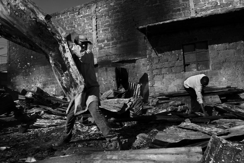 Fire is disastrous in the slum as shanties are so densely located and built from largely flammable materials. Footpaths, the only means of moving through the slum are not wide enough to accomodate fire trucks, leaving residents to fight blazes with buckets of water fetched from the Mathare River.Here, a street boy is paid to pick up sheets of corrugated metal the morning after a fire. Such sheets will be reused as siding, but new sheets without holes much be purchased for roofing. When standing on the rim of the Mathare Valley slums, one can pick out which areas of the slum have suffered a fire recently by looking for patches of shiny, new roofing.